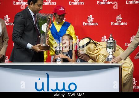 Dubai, UAE. 8th March, 2014. Sheikh Mohammed Bin Khalifa Al Maktoum kisses the children of jockey Christophe Soumillon - Stock Photo