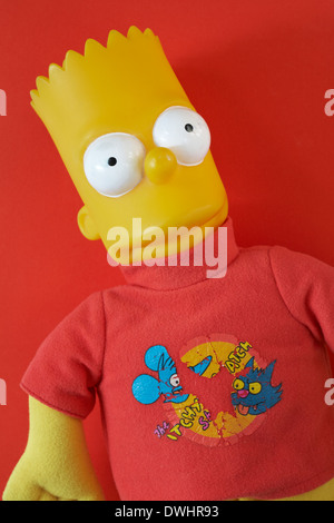 well worn Bart Simpson plastic doll set against red background - Stock Photo