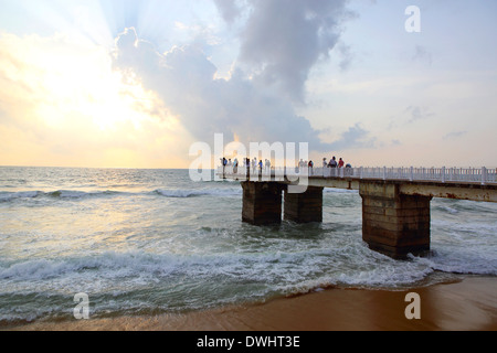 People watching sunset on pier at Galle Face beach in Colombo, Sri Lanka - Stock Photo