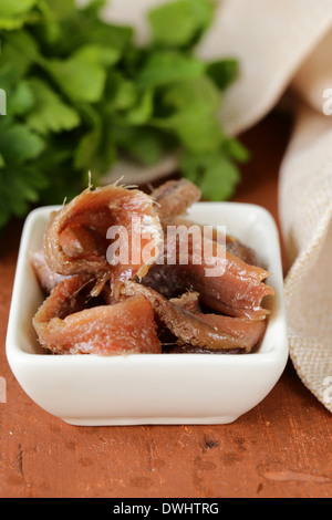 Canned marinated anchovies fillets in a white bowl - Stock Photo