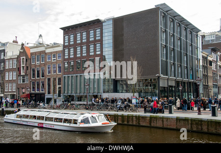 Exterior of Anne Frank House museum in Amsterdam with tourists and canal boat - Stock Photo