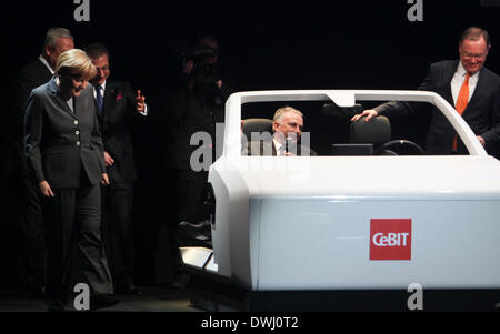 Hanover, Germany. 9th Mar, 2014. German Chancellor Angela Merkel (1st L) views a model of an Audi driverless car during the opening ceremony of the CeBIT tech fair in Hanover, Germany, March 9, 2014. German Chancellor Angela Merkel and British Prime Minister David Cameron jointly opened CeBIT, one of the world's largest IT fairs, in western German city of Hanover on Sunday. © Zhang Fan/Xinhua/Alamy Live News