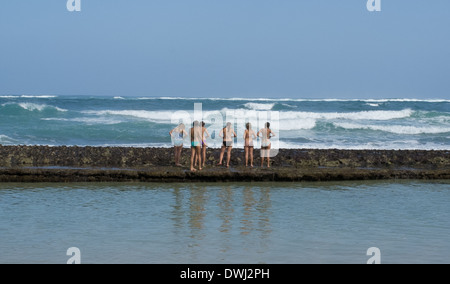 Girls on a reef. Color photo of six girls in two piece bathing suits on a reef, backs to camera, facing ocean - Stock Photo