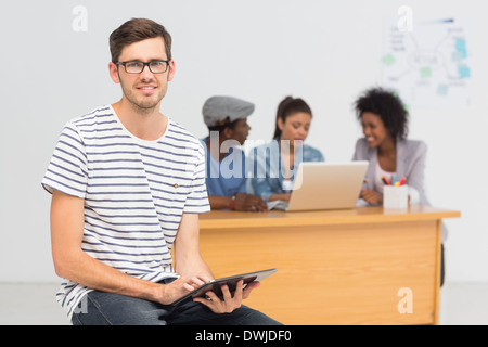 Artist using digital tablet with colleagues in background at office - Stock Photo