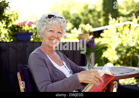 Senior woman sitting on a chair in backyard garden holding a book and looking at camera smiling - Stock Photo