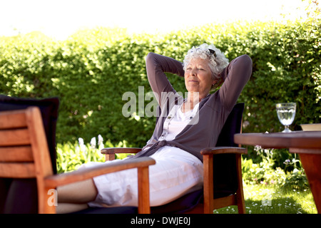 Senior woman sitting on a chair and taking a nap in backyard. Elder woman sleeping in backyard garden - Stock Photo