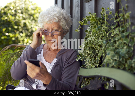 Senior lady sitting on a bench with her reading glasses in her backyard reading text message on her mobile phone - Stock Photo