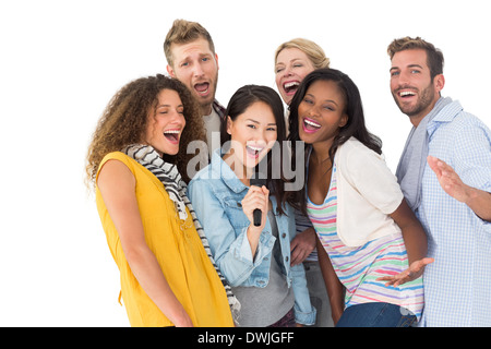 Happy group of young friends having fun doing karaoke - Stock Photo