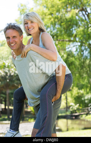 Man giving piggyback ride to woman - Stock Photo