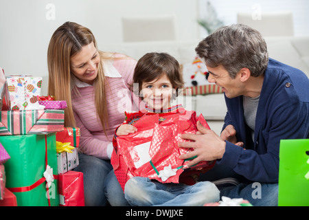 Boy And Parents Opening Christmas Present - Stock Photo
