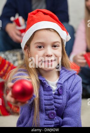 Smiling Girl Showing Christmas Ornament - Stock Photo