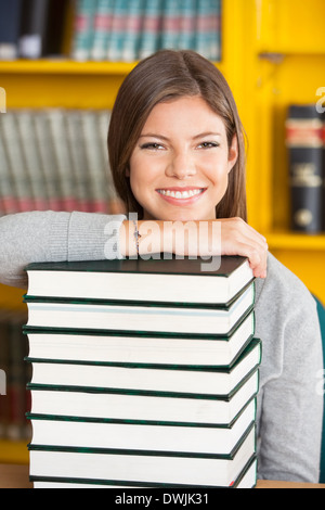 Happy Woman Resting Chin On Stacked Books In Library - Stock Photo