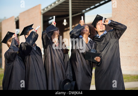 Students In Graduation Gown Looking Through Certificates On Camp - Stock Photo