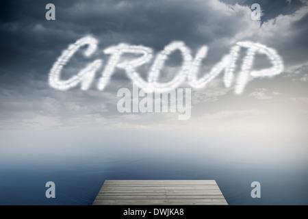 Group against cloudy sky over ocean - Stock Photo