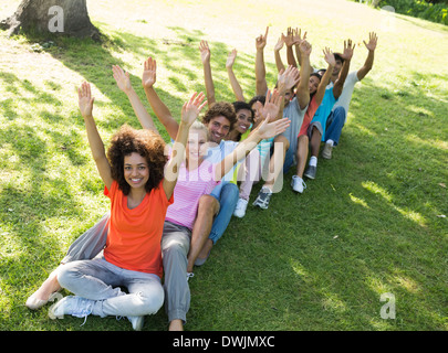 Row of excited friends raising hands in park - Stock Photo