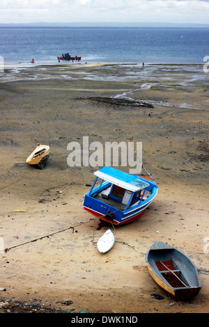 A crew of fishermen unloading the vessel at the seaside during the low tide in Northern Mozambique. - Stock Photo
