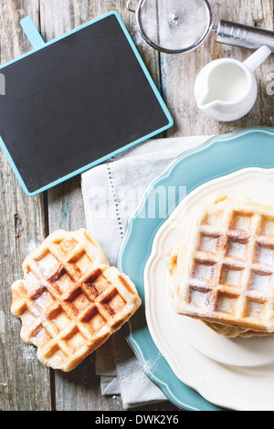 Top view on plates with fresh belgian waffles served with empty black chalkboard over old wooden table. - Stock Photo
