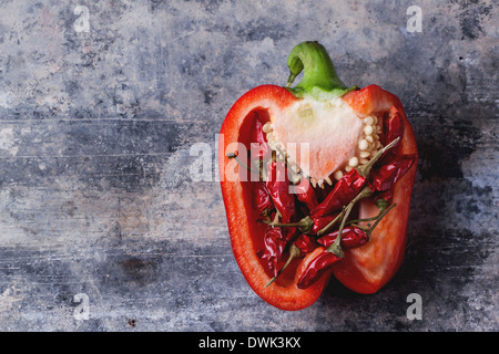 Half of raw red pepper stuffed by little red hot chili peppers over vintage background. - Stock Photo