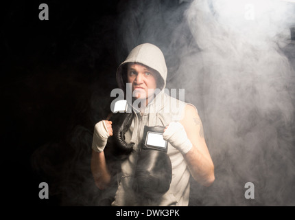 Mean looking ambitious young boxer psyching himself up before a match flexing his fist and snarling in a dark smoky - Stock Photo