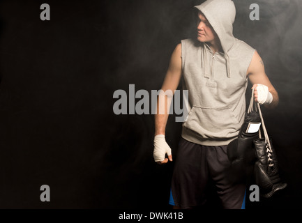 Young boxer arriving for a fight walking carrying his gloves by the laces in his bandaged hand and looking to the - Stock Photo