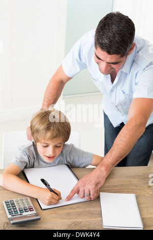 Father assisting boy in solving maths - Stock Photo