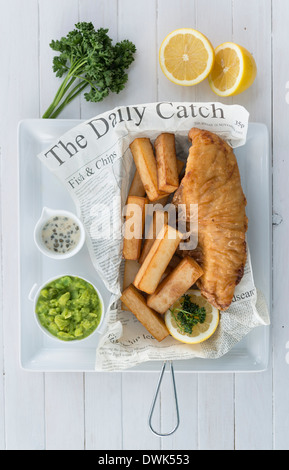 Fish and chips served in a newspaper in a restaurant - Stock Photo