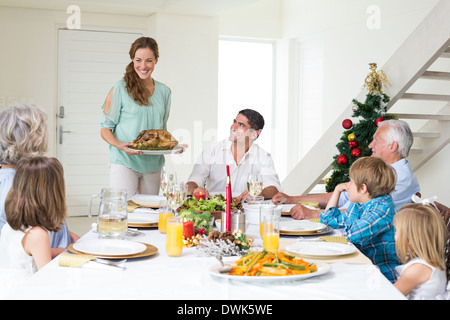 Mother serving Christmas meal to family - Stock Photo