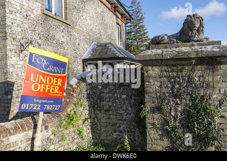 Decorative lion statue on garden wall surrounding a house that is under offer - Stock Photo