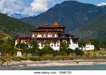 The Punakha Dzong is seen across the Mo Chhu River in central Bhutan while Buddhist prayer flags flutter nearby - Stock Photo