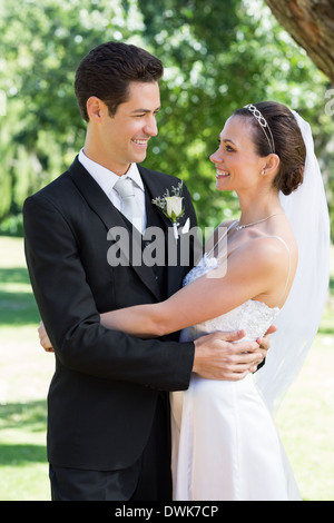 Newly wed couple embracing each other in garden - Stock Photo