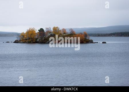 Small island of Inari lake in autumn colors, Finland - Stock Photo