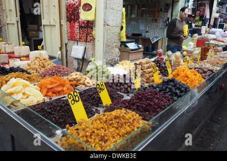 A seller standing behind his display of dried fruits for sale at Mehane Yehuda Market, Jaffa St, Jerusalem, Israel - Stock Photo