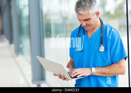 modern senior doctor working on a laptop - Stock Photo