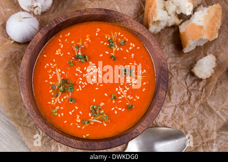 tomatos soup puree in wooden bowl on crushed brown paper - Stock Photo