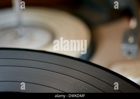 Gramophone vinyl record against old record player in the background. Concept photo of retro music and sound - Stock Photo