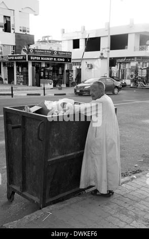 Man looking through a bin on the tourist strip in Hurghada, Egypt - Stock Photo