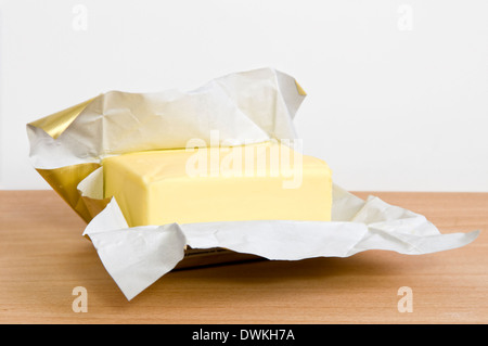 Open pack of butter on wooden chopping board - Stock Photo
