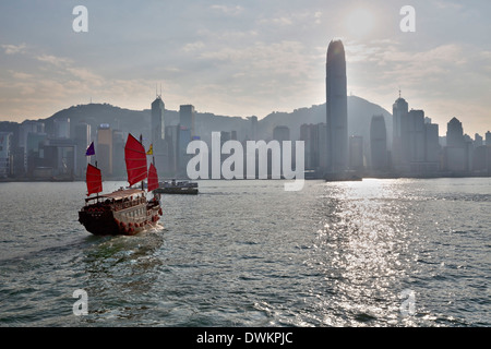 Aqua Luna Junk boat in Victoria harbour with Hong Kong skyline, Hong Kong, China, Asia - Stock Photo