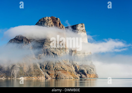 Fog lifting on the steep cliffs of Icy Arm, Baffin Island, Nunavut, Canada, North America - Stock Photo