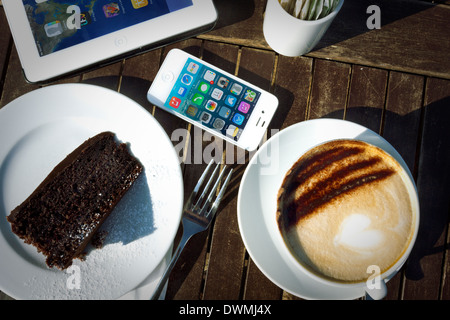 iPhone 4s, iPad 2 And Cake And Cappuccino On Table In Sunlight - Stock Photo
