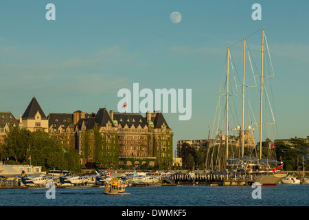 Nearly Full moon rising behind Empress hotel and Inner harbor-Victoria, British Columbia, Canada. - Stock Photo