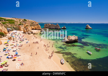 Holidaymakers sunbathing on Praia da Dona Ana, sandy beach near the resort of Lagos, Algarve, Portugal, Europe - Stock Photo