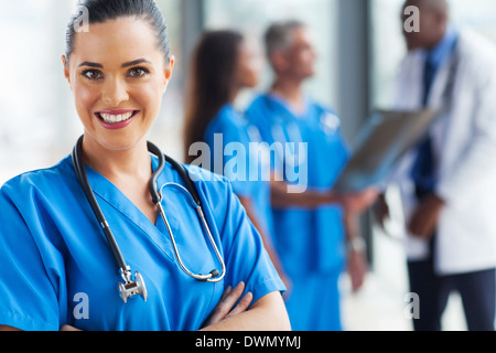 smiling young doctor looking at the camera with colleagues on background - Stock Photo