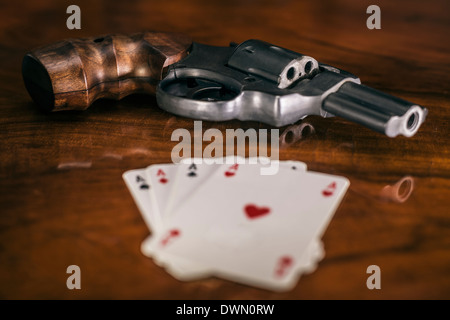 Risky gambling concept. Gun and four aces cards on wooden table. - Stock Photo