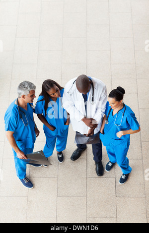 overhead view of doctors looking at patient's x-ray - Stock Photo