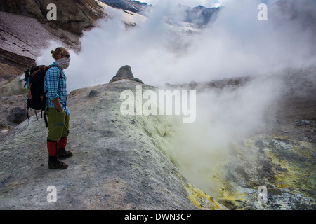 Tourists standing by smoking fumaroles on Mutnovsky volcano, Kamchatka, Russia, Eurasia - Stock Photo