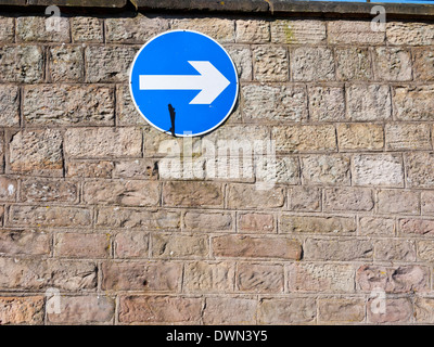 One way street sign on a stone wall, UK. - Stock Photo