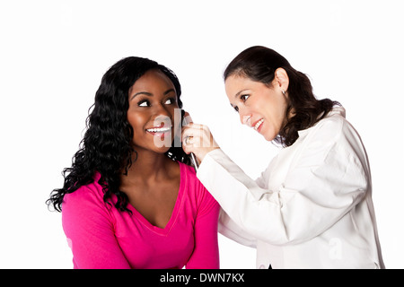 Happy smiling doctor physician checking patient ear for infection with otoscope, isolated. - Stock Photo