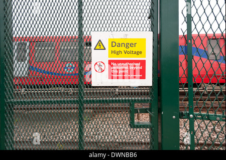 Danger high voltage only safe railway crossing is a closed one risk of electrocution security fencing DLR trainline - Stock Photo