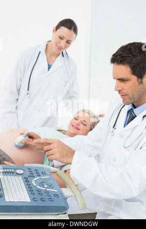 Excited pregnant woman having an ultrasound scan - Stock Photo